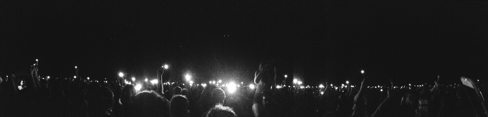 Panoramic Shot Of Crowd In Music Concert Against Sky At Night