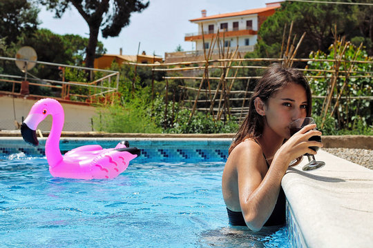 Woman drinking a soda in the pool.
