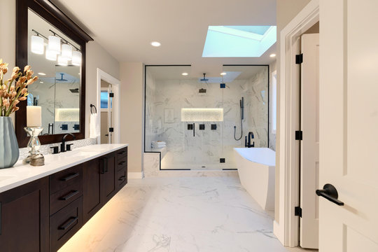 Luxury modern home bathroom interior with dark brown cabinets, white marble, walk in shower, free standing tub.