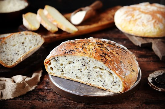 Homemade bread assortment: corn, with sesame seeds and chia seeds on a dark wooden background. rustic