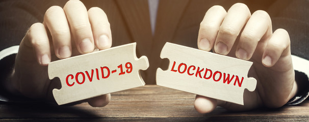 A man collects wooden puzzles with the words Covid-19 and Lockdown. Coronavirus pandemic infection...