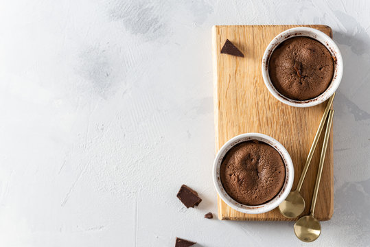 Delicious fresh fondant with hot chocolate centre in ceramic molds on wooden board on white background. Lava cake recipe, menu. Top view, copy space