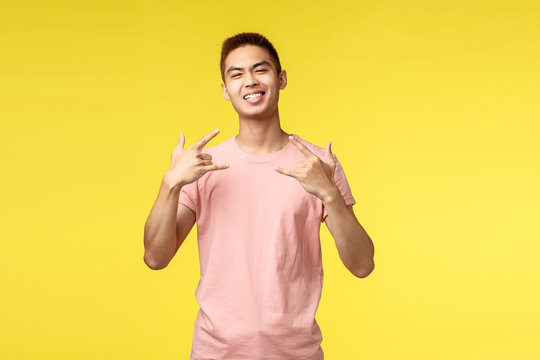 Portrait of cool and proud good-looking asian guy with big ego, show rock-n-roll or heavy metal sign and smiling, enjoying awesome concert, having fun on music festival, yellow background