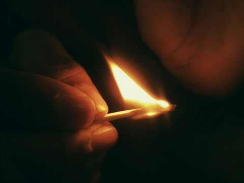 Cropped Hand Holding Lit Matchstick