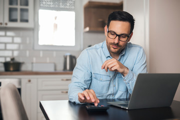 Young accountant count on calculator at home.