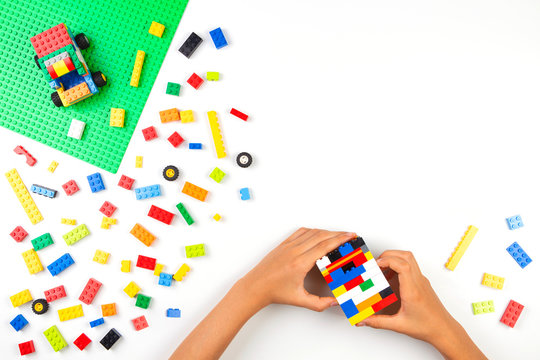 Vilnius, Lithuania - 17 August, 2019: Child hands playing with colorful Lego bricks blocks on white table