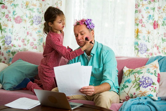 Child playing and disturbing father working remotely from home. Little girl applying makeup with brush. Man sitting on couch with laptop. Family spending time together indoors.