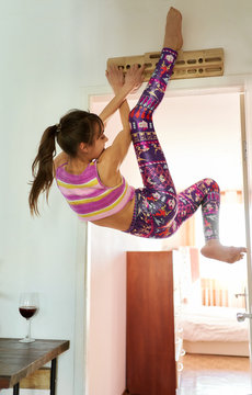 flexible slim woman training at home during quarantine, female climber doing exercises on campus board in her apartment.