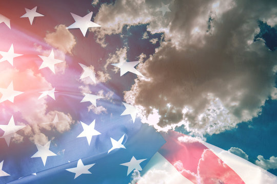 Flag of the United States of America against a background of blue sky and clouds.