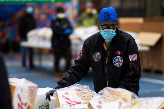 People receive food at a City Harvest Mobile Market Food Distribution Center in Brooklyn, New York