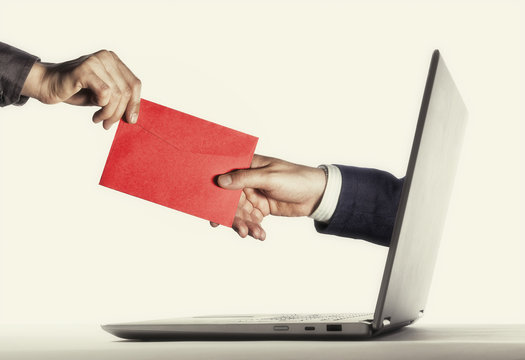 The human hand with envelope stick out of a laptop screen. Concept of correspondence, feedback, advertising via internet.