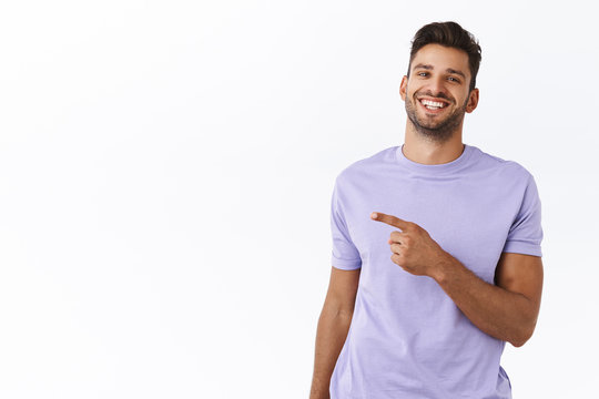 Outgoing, happy handsome hipster man pointing left, showing where get excellent tourist trip offer to have journey on holidays. Satisfied smiling man in purple t-shirt recommend promo