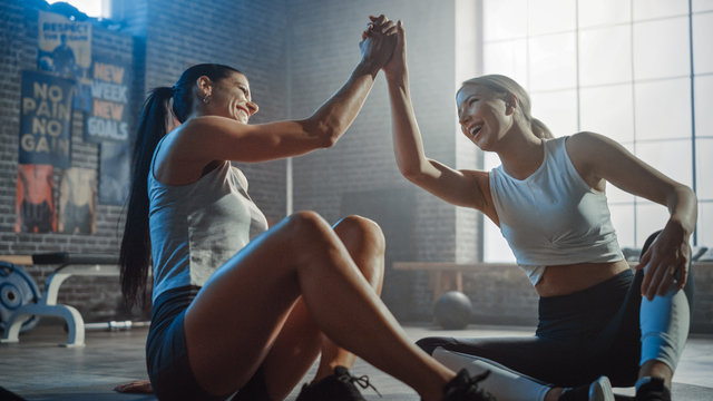 Two Beautiful Fit Athletic Girls Sit on a Floor of Industrial Loft Gym. They're Happy with their Training Program and Successfully Give a High Five.