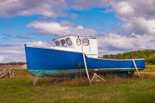 Fishing boat on moored on dry land for repairs on summer's day in rural Cape Breton, Nova Scotia, Canada.