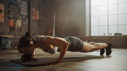 Strong and Fit Athletic Woman in Sport Top and Shorts is Doing Push Up Exercises in a Loft Style Industrial Gym with Motivational Posters. It's Part of Her Cross Fitness Training Workout. Warm Light.