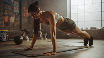 Strong and Fit Athletic Woman in Sport Top and Shorts is Doing Push Up Exercises in a Loft Style...
