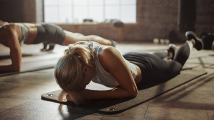 Foto op Aluminium Fitness Shot of Two Strong Fit Athletic Women Hold a Plank Position in Order to Exercise Their Core Strength. Blond Girl is Exhausted and Fails the Training First. They Workout in a Loft Gym.