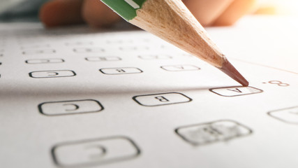 On Exam Test Person Colors Right Answers with a Pencil. Filling up Answer Sheet with Standardized Tests, Marking Correct Answer Bubbles