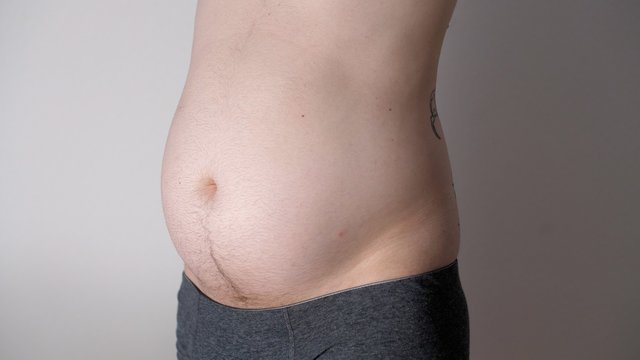 Fat male stomach. Weight loss or weight gain during quarantine. Attractive man with bare belly. Close-up of male beer belly of sexy man. Bodypositive