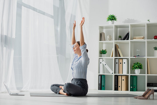 young businesswoman having online classes on laptop and practicing yoga in lotus position on mat with hands up in office