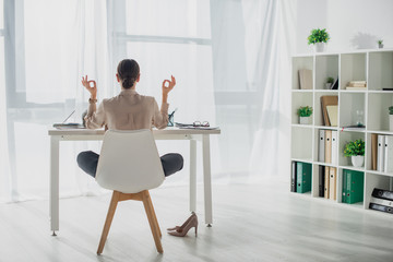 Back view of businesswoman meditating in lotus pose with gyan mudra at workplace