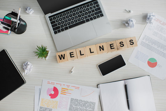 top view of workplace with business documents, laptop, smartphone and alphabet cubes with wellness word