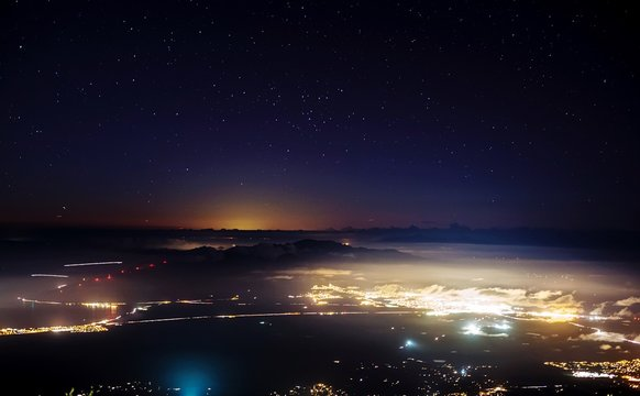Scenic View Of Illuminated Maui Island Against Star Field At Night