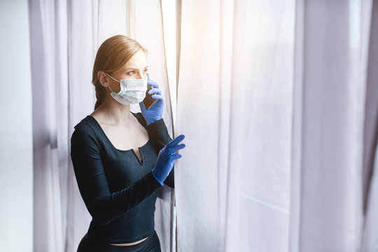 Woman in quarantine looking out of window using phone