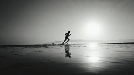 Fototapeta Silhouette Man Running In Water At Beach