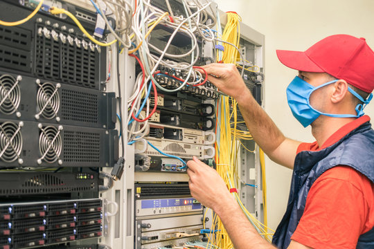 A man in a red cap works in a datacenter. A technical employee maintains computer equipment. A technician in a medical mask switches wires in the server room.