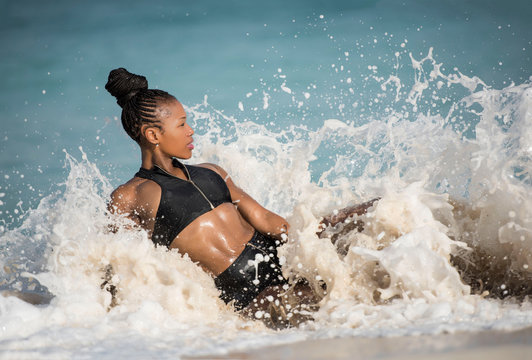 Beautiful African American Black female fitness model on the beach wearing black sportswear sitting on the water's edge being splashed by a large wave.