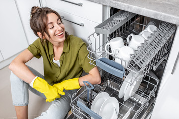 Portrait of a happy housewife sitting near the dishwasher with clean dishes on the kitchen at home. Easy house work with kitchen appliances concept