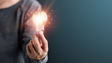 Hand of man holding illuminated light bulb, idea, innovation and inspiration concept.concept creativity with bulbs that shine glitter.