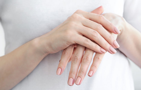 Close up of female hands with gently beige manicure. Hand skin care.