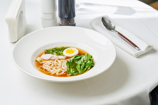 Ramen soup with soft boiled egg and noodles on light background