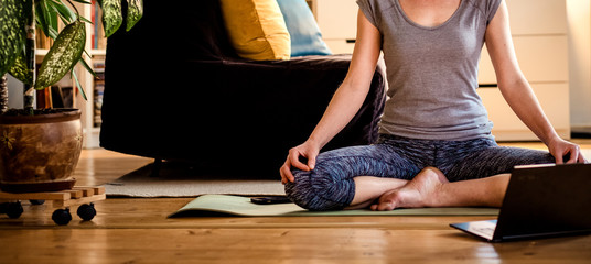 woman doing yoga workout at home watching videos online on laptop computer