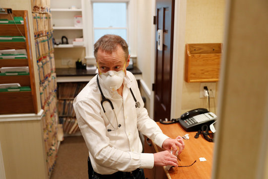 Dr Greg Gulbransen wipes his glasses while talking to a patient as he maintains visits with both his regular patients and those confirmed to have the coronavirus disease (COVID-19) at his pediatric practice in Oyster Bay, New York