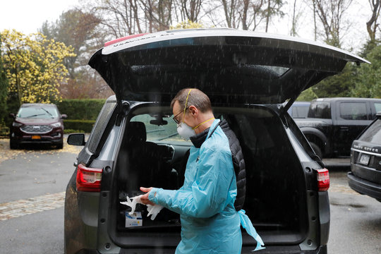 Dr Greg Gulbransen dons personal protective gear for a home call with a patient who had earlier been confirmed to have the coronavirus disease (COVID-19) as he maintains visits with both his regular patients and those with the virus in Oyster Bay, New York