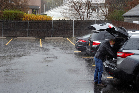 Dr Greg Gulbransen removes equipment from his car after a house call as he works to maintain visits with both his regular patients and those confirmed to have the coronavirus disease (COVID-19) at his pediatric practice in Oyster Bay, New York