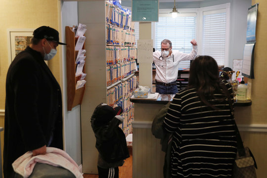 Dr Greg Gulbransen gestures to a toddler after a checkup for his daughter while maintaining visits with both his regular patients and those confirmed to have the coronavirus disease (COVID-19) at his pediatric practice in Oyster Bay, New York