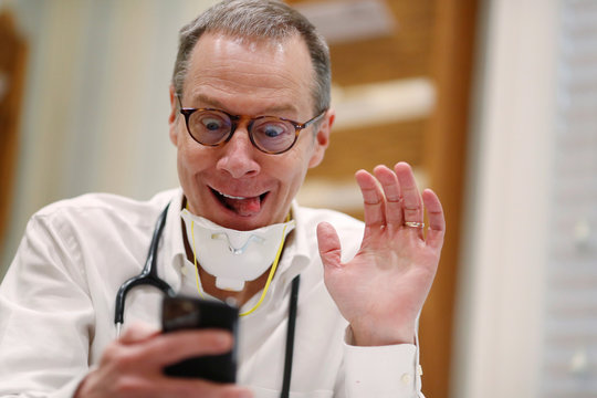 Dr Greg Gulbransen takes part in a telemedicine call with a patient while maintaining visits with both his regular patients and those confirmed to have the coronavirus disease (COVID-19) at his pediatric practice in Oyster Bay, New York