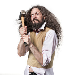 Portrait of an eccentric, aggresive man holding a hammer