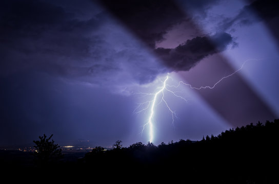 Low Angle View Of Thunderstorm Over Silhouette Trees Against Sky At Night