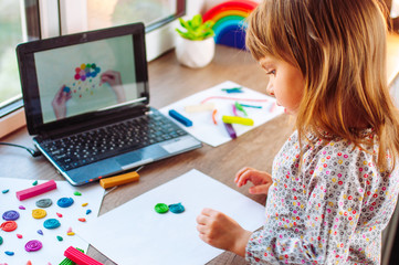 Little girl molding colorful clay cloud watching online learning lesson Fotomurales