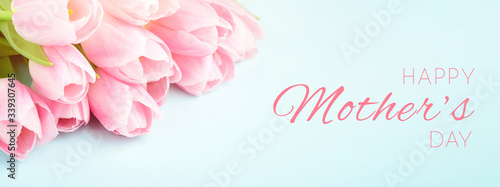 Tender pink tulips on blue background. Happy Mother's Day greeting card, banner for website.