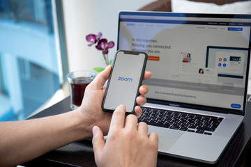 Man hand Macbook and iPhone calling Zoom Video Communications application