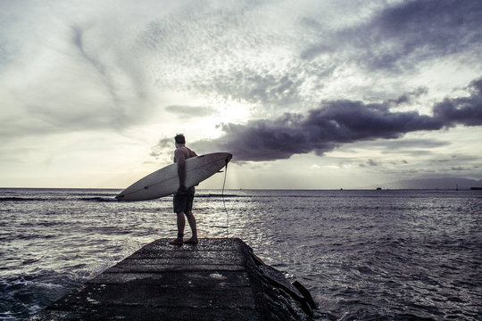 Man Carrying Surfboard Standing On Rock In Sea Against Sky