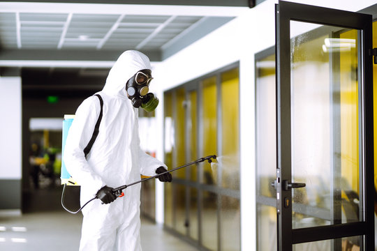 Disinfecting of office to prevent COVID-19, Man in protective hazmat suit with  with spray chemicals to preventing the spread of coronavirus, pandemic in quarantine city. Cleaning concept.