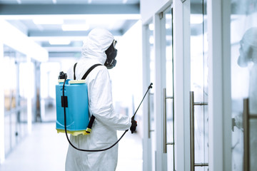Disinfecting of office to prevent COVID-19, Man in protective hazmat suit with  with spray...