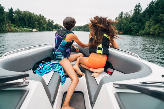 Girls in life jackets sitting on bow of boat on lake surrounded by trees